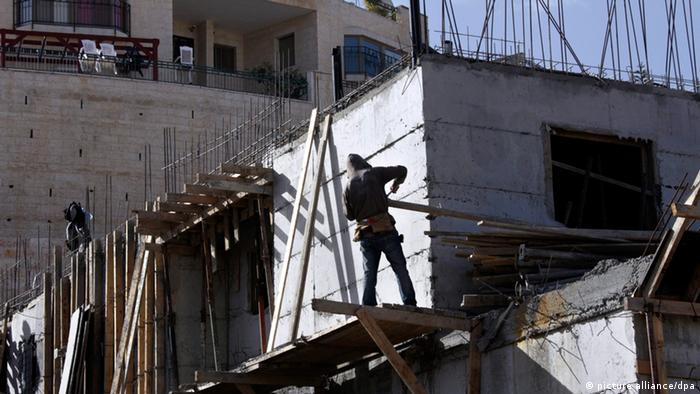 epa03460234 A photograph released on 06 November 2012 shows a Palestinian at a building site in the East Jerusalem neighborhood of Pizgat Ze'ev, 08 January 2012. Israel announced on 06 November, 2012, the US election day, that it intends to build an additional 1,285 new housing units in the West bank settlement of Ariel (72 units) and in Pizgat Ze'ev (607 units) and the East Jerusalem neighborhood of Ramot (606 units). Many consider both Pizgat Ze'ev and Ramot to be Jewish settlements as they are built on what was Arab land before the 1967 war. EPA/JIM HOLLANDER