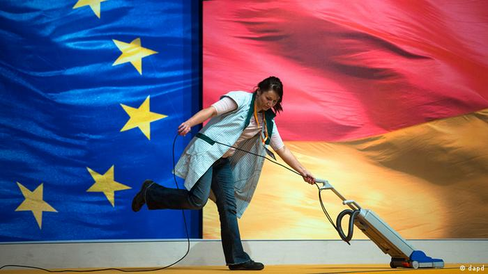 At the eve of Germany's Christian Democratic Party, CDU, 2012 convention a worker cleans the floor in front of a huge European and German flag at the plenary hall in Hannover, Monday, Dec. 3, 2012. The ruling CDU will elect a new board and reelect Chancellor Angela Merkel as the party's chairwoman during the two-day convention. (Foto:Markus Schreiber/AP/dapd)
