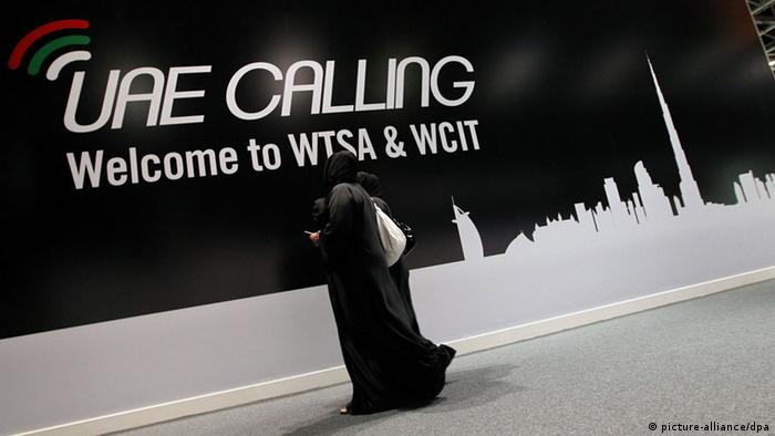 Two women pass in front of a placard for the World Conference on International Telecommunications (WCIT) in Dubai (EPA/ALI HAIDER)
