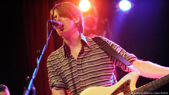 Stephen Malkmus sings into a microphone on stage