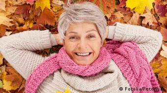Seniorin liegt in bunten Laub (Foto: Fotolia.com)