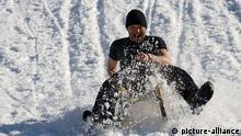 Symbolbild Mann Schlitten rutschen Schnell Schlitten fahren Bergab rodeln Winter Berg Hang Holzschlitten Freizeit