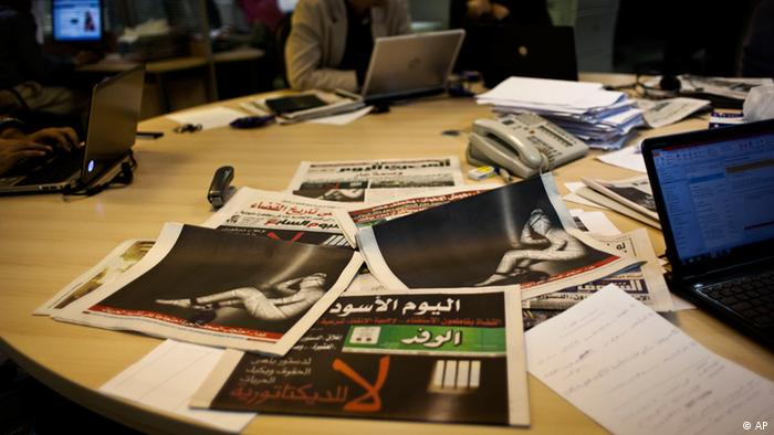 "Egyptian journalists at the editorial room of Al-Masry Al-Youm daily newspaper next to copies of Egypt's most prominent newspapers running black background front pages with Arabic that reads, ""no to dictatorship, tomorrow free newspapers will obscure to protest the freedom's restrictions,"" and a picture of a man wrapped in newspapers with his feet cuffed, in Cairo (Photo: Nasser Nasser/AP/dapd)"