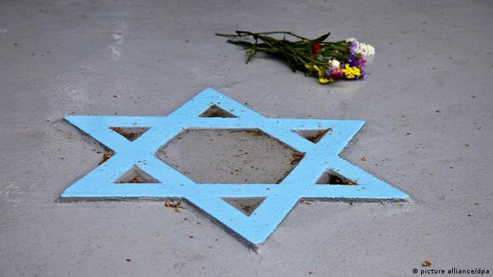 A bunch of summer flowers lies next to the star of David in the memory of the victims of the Holocaust 70 years after, at the Jewish cemetery in Iasi, Romania