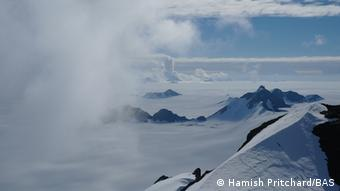 The Antartic is difficult terrain for scientists to access. Here, clouds cross ice-covered polar mountains.
