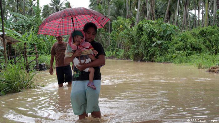 GettyImages 157537742 A woman carrying her child wades through a flooded road brought about by heavy rains due to Typhoon Bopha, as she evacuates to a safer place, in Pantukan town, Compostela Valley province, in southern island of Mindanao on December 4, 2012. Typhoon Bopha killed 43 people in one hard-hit Philippine town December 4, local television station ABS-CBN reported from the scene. AFP PHOTO (Photo credit should read STR/AFP/Getty Images)
