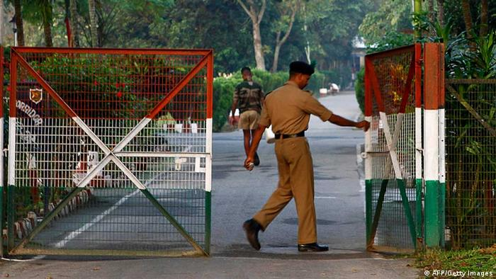 TO GO WITH Bangladesh-India-border-history-enclaves,FEATURE by Shafiq AlamIn this photograph taken on December 10, 2010, an Indian security official opens the gate of Indian ruled Rangpur some 350 kms north from Dhaka. Little bits of India are in Bangladesh, and little bits of Bangladesh are in India. The existence of 'enclaves' on either side of the border is a bizarre anomaly that might finally be solved by a swap. The islands of land result from ownership arrangements made centuries ago between local princes, surviving partition of the sub-continent in 1947 after British rule, and Bangladesh's 1971 war of independence with Pakistan. AFP PHOTO (Photo credit should read STRDEL/AFP/Getty Images)