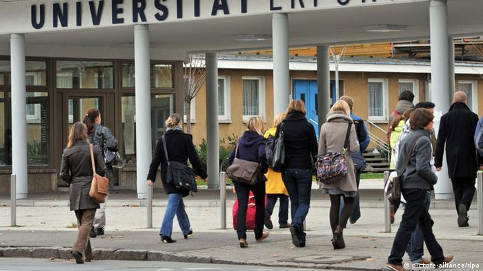 Studierende betreten das Universitätsgelände.