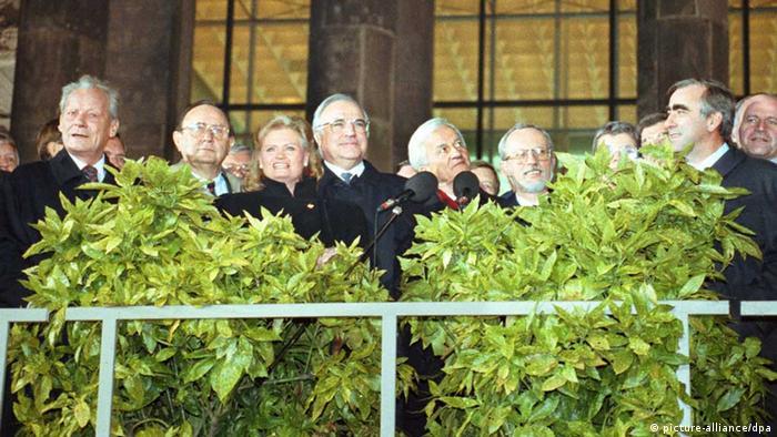 Die Deutschen sind wieder vereint: Bei der Berliner Feier am 03.10.1990 winken von der Freitreppe des Reichstagsgebäude (l-r): Alt-Bundeskanzler Willy Brandt (SPD), Bundesaußenminister Hans-Dietrich Genscher (FDP), Hannelore Kohl, Bundeskanzler Helmut Kohl (CDU) und Bundespräsident Richard von Weizsäcker, daneben Lothar de Maiziere, der letzte DDR-Ministerpräsident und links im Profil Theo Waigel (CSU) (Foto: dpa)