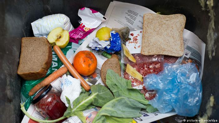 A trash can is filled with edible foodstuffs such as a sandwich, an orange, a half-eaten apple and bread. (Photo: Patrick Pleul/dpa)
