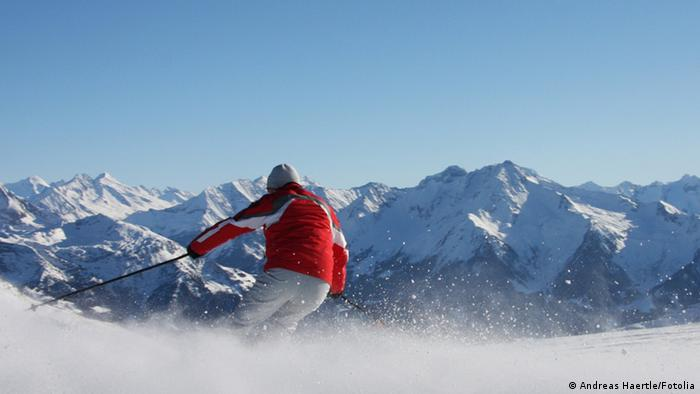 Man skiing down a slope in the Alps