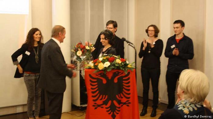 preisverleihung an Prof. Peter Bartl in albanien Prof. Peter Bartl wird nach dem Vortrag ein Blumenstraß überreicht Dezember 2012