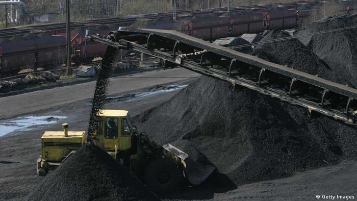 An aerial conveyor belt dumps black coal into a yellow truck. (Photo: Sean Gallup/Getty Images)