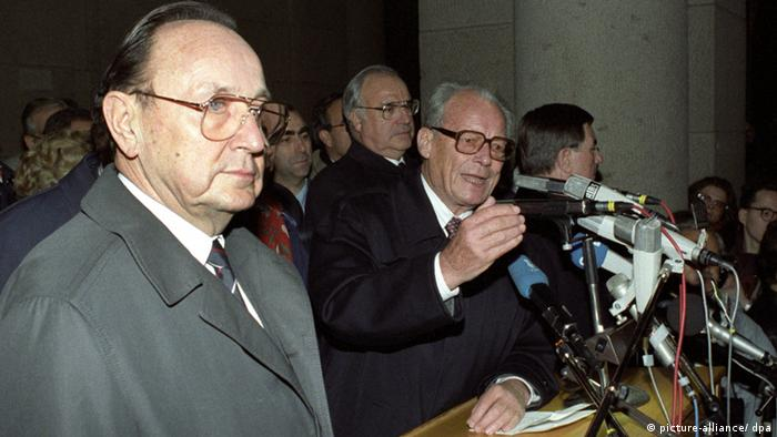 Former Chancellor Willy Brandt (SPD) giving a speech after the Berlin Wall was opened in November 1989 To his left then foreign minister Hans-Dietrich Genscher (FDP) and behind Brandt Chancellor Helmut Kohl (CDU).