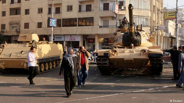 Supporters of the Muslim Brotherhood walk past tanks that were just deployed outside the Egyptian presidential palace in Cairo December 6, 2012. (Photo via Reuters)