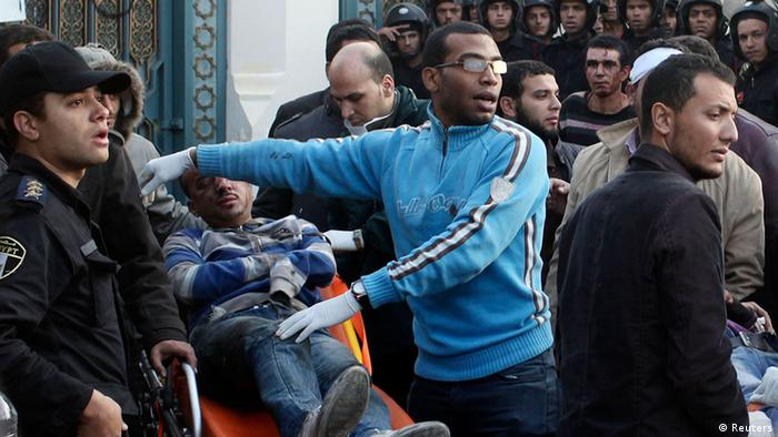 A clean-cut Egyptian man wearing a bright blue sweatshirt and modern eyeglasses points at an injured man next to him on a stretcher. (Photo: REUTERS/Asmaa Waguih)