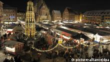 Stands and visitors enjoy the twinkling lights at the Nuremberg Christmas market (picture-alliance/dpa)