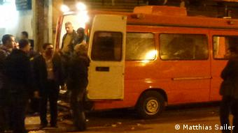 A handful of people stand next to an orange and white ambulence in the night time (Photo: Matthias Sailer, Journalist, Political Scientist)
