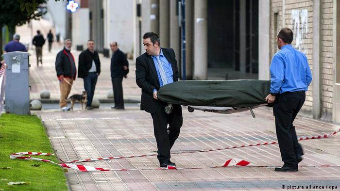 Morticians carry the body of a woman, 53, after she had thrown herself out of a window EPA/MIGUEL TONA +++(c) dpa - Bildfunk+++