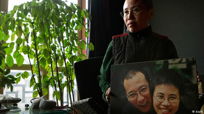 Liu Xia, wife of 2010 Nobel Peace Prize winner Liu Xiaobo, poses with a photo of her and her husband during her first interview in more than two years at her home in Beijing, China, on Thursday, Dec. 6, 2012. Liu trembled uncontrollably and cried Thursday as she described how her confinement under house arrest has been absurd and emotionally draining in the two years since her jailed activist husband was named a Nobel Peace laureate. (Foto:Ng Han Guan/AP/dapd)