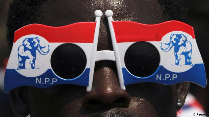 An NPP supporter wears glasses in the party colors of red, white and blue