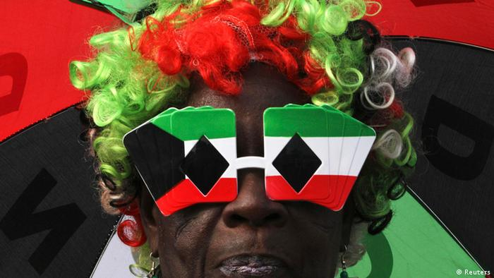 A NDC supporter wears glasses and a wig in the party colors of green, white and red