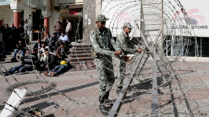 Supporters of Egyptian president Mohammed Morsi, left, sit as Egyptian Army soldiers lay barbed wire near the presidential palace to secure the site of overnight clashes between supporters and opponents of President Mohammed Morsi in Cairo