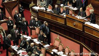 A rose-colored section of Italy's senate shows a dozen parliamentarians in black suits discussing a recent vote. (Photo:EPA/GIUSEPPE LAMI)