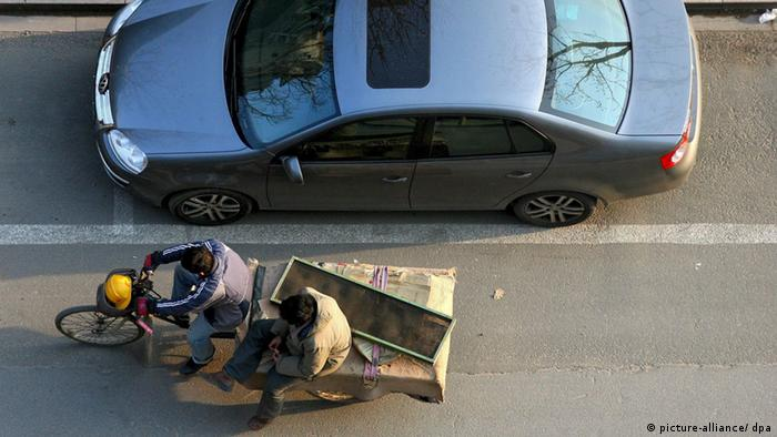 Chinese migrant workers pass a parked car with a bicycle in central Beijing, China, 30 March 2008.
