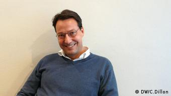 A smiling middle-aged man wearing a blue sweater, white collared shirt and dark eye glasses looks at the camera against a white backdrop.