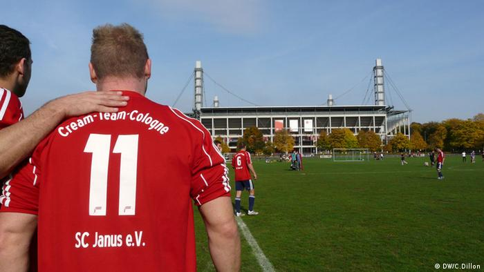 One soccer player places his hand around another's back for support - or perharps romantically - as they look into the distance at a large professional soccer stadium. Der Fotograf / die Fotografin ist (freie) Mitarbeiter(in) der DW
