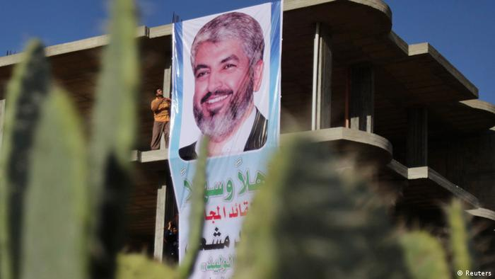 A Palestinian man hangs a poster depicting Hamas chief Khaled Meshaal in Rafah, in the southern Gaza Strip December 6, 2012. . REUTERS/Ibraheem Abu Mustafa (GAZA - Tags: POLITICS)