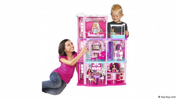 Boy and girl play with Barbie house