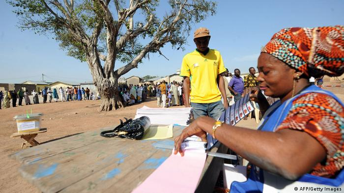 An electoral officer hands out ballot papers in the 2012 election