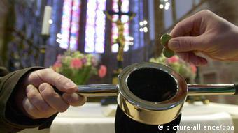 Ein Kirchenbesucher steckt einige Münzen in den Klingelbeutel. Foto: dpa