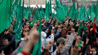 Palestinian Hamas activists raise their fingers while chanting Islamic slogans as other wave green Islamic flags during a rally to commemorate the 25th anniversary of the Hamas militant group, in Gaza city, Saturday, Dec. 8, 2012. Hamas chief Khaled Mashaal is expected to speak at Saturday's rally in Gaza City after entering the seaside strip a day earlier after a long exile from Palestinian territory. (Foto:Adel Hana/AP/dapd)