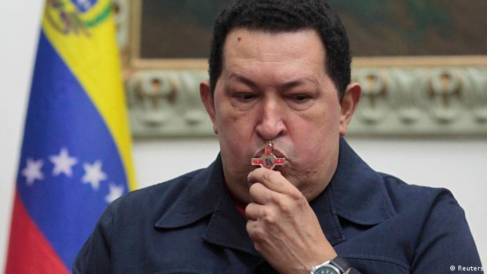 REFILE - CORRECTING DATE Venezuelan President Hugo Chavez kisses a crucifix as he speaks during a national broadcast at Miraflores Palace in Caracas December 8, 2012. Chavez said on Saturday he would undergo another cancer operation in the coming days after doctors in Cuba found a third recurrence of malignant cells in his pelvic area. The news is a big blow for his supporters in South America's biggest oil exporter, who elected him in October to a new six-year term in power. Chavez has twice said he was cured, and then had to return to Cuba for more surgery. In a televised broadcast flanked by ministers at the Miraflores presidential palace, Chavez said that if anything happened to him and a new vote had to be held, his supporters should vote for Vice President Nicolas Maduro - the first time the socialist leader has named a successor. REUTERS/Miraflores Palace/Handout (VENEZUELA - Tags: POLITICS)