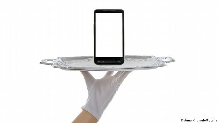 Gloved hand holding a cell phone on a silver platter