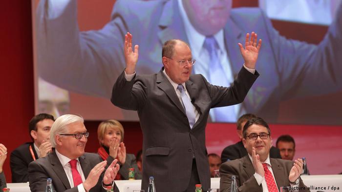 SPD-Kanzlerkandidat Peer Steinbrück steht mit erhobenen Händen am 09.12.2012 beim außerordentlichen Bundesparteitag der SPD in Hannover neben Frank-Walter Steinmeier (l), Fraktionsvorsitzender der SPD-Bundestagsfraktion, und Sigmar Gabriel (r), SPD-Vorsitzender, die ihm beide applaudieren, Foto: Michael Kappeler/ dpa