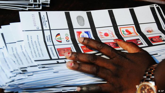 A close-up of a hand holding ballot papers