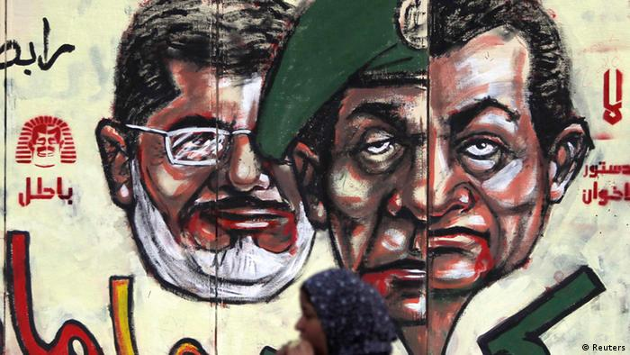 Anti-Mursi protester eats in front of graffiti with ( R to L ) Egypt's former president Hosni Mubarak, former Field Marshal Mohamed Hussein Tantawi and Egypt's President Mohamed Mursi on the wall of the presidential palace in Cairo, December 8, 2012.