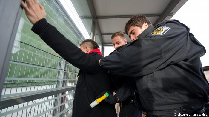 Ein Polizist zieht während eines Pressetermins im Rahmen einer Polizeiübung einem Mann ein Bengalo aus der Tasche (gestellte Szene). (Foto: Marijan Murat/dpa)