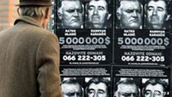 A man stands in front of a wanted poster for Karadzic and Mladic