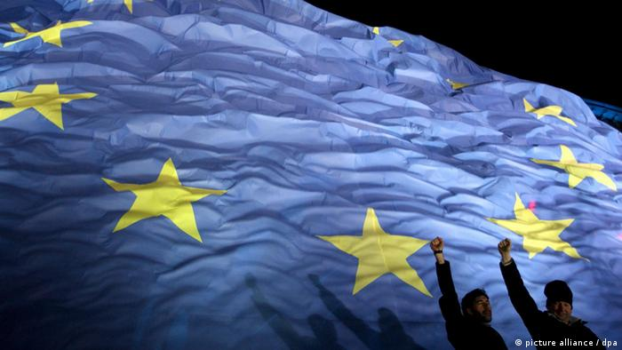 A blue flag with yellow stars shows the shadow of a man standing on front of it with his arm raised (Photo: EPA/ROBERT GHEMENT)