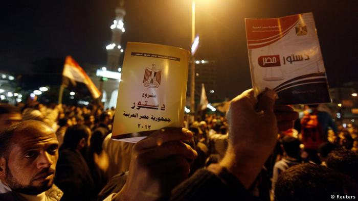 Supporters of Egyptian President Mohamed Mursi and members of the Muslim Brotherhood chant pro-Mursi slogans with copy of Egypt Constitution during a rally in front of Rabaa El Adaweya Mosque square in Cairo, December 9, 2012. Egypt's main opposition coalition rejected on Sunday Islamist President Mohamed Mursi's plan for a constitutional referendum this week, saying it risked dragging the country into violent confrontation. REUTERS/Amr Abdallah Dalsh (EGYPT - Tags: POLITICS CIVIL UNREST)
