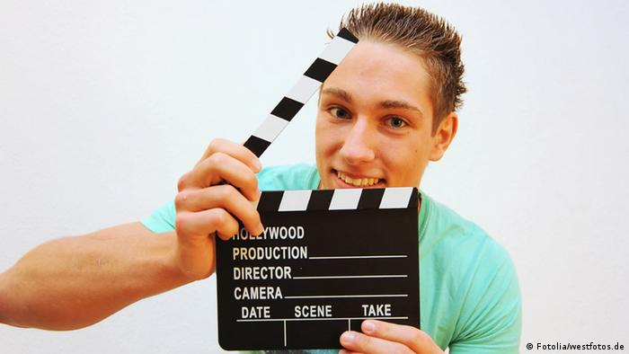 Young man holds a clapperboard, Copyright: Fotolia/westfotos.de