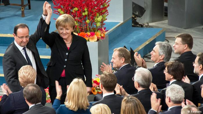 German Chancellor Angela Merkel and French President Francois Hollande hold their hands up during the Nobel Peace Prize ceremony at the City Hall in Oslo December 10, 2012.
