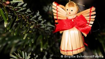 An angel christmas tree decoration hanging on a Christmas tree