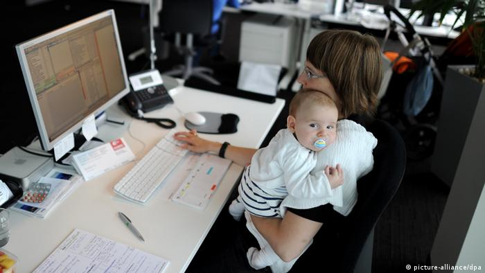 A woman holds her baby as she works at a computer (Photo: Tim Brakemeier)