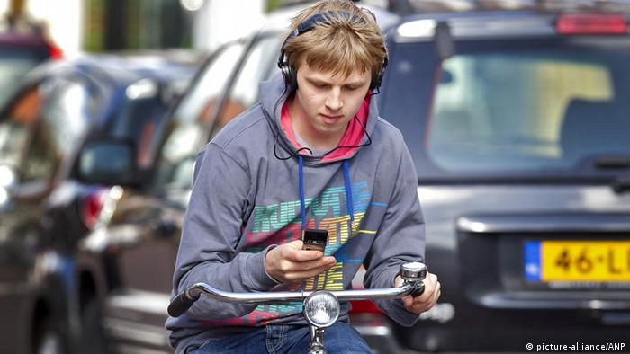 Radfahrer mit Handy und Kopfhörern im Straßenverkehr
